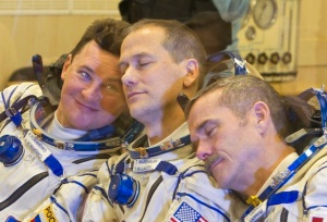 International Space Station crew members Russian cosmonaut Romanenko, U.S. astronaut Marshburn and Canadian astronaut Hadfield joke as they talk with relatives after putting on their space suits at the Baikonur cosmodrome